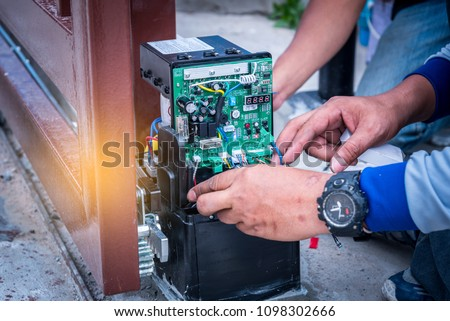 Technician assembling and testing motor automatic gate for home security system. #1098302666