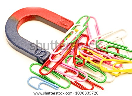 horseshoe magnet attracting colorful paper clips isolated on white background