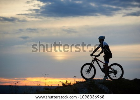 Sport and recreational activities at fresh air under evening sky. Incognito cyclist sitting on bicycle and riding bike in twilight. Active man posing and wearing sportswear and helmet. #1098336968