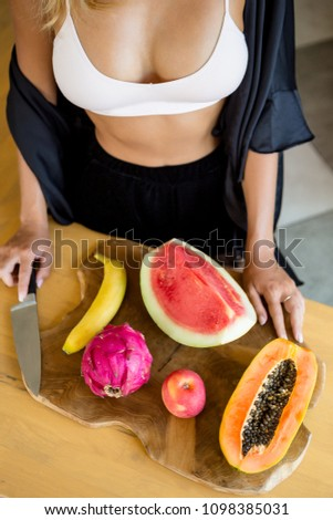 Sexy lady with tasty fruits on a kitchen. Papaya, Carica, apple, watermelon, dragon fruit. Healthy eating lifestyle concept. Health care and beauty. Healthy breakfast. Fitness food. Proper nutrition. #1098385031