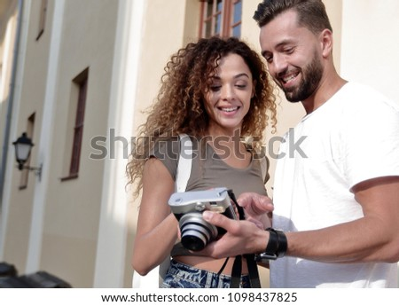 Portrait of young friends walking looking at the photos #1098437825