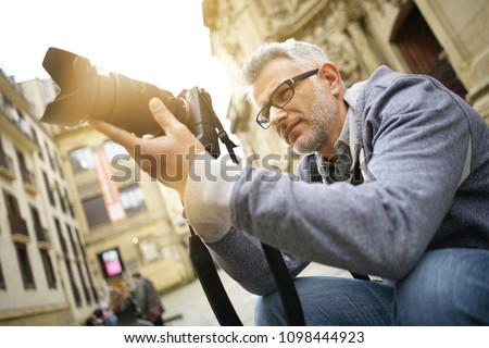 Photographer in European city taking picture of buildings