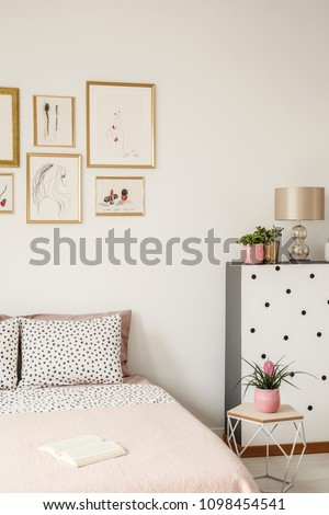 Cropped photo of bed with pillows, paintings and plants in a bedroom interior #1098454541