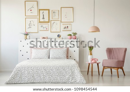 Dotted, double bed, paintings with gold frames and pink armchair set in a serene bedroom interior #1098454544