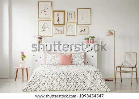 Bright bedroom interior with dotted sheets, headrest, double bed, gold accents and art gallery above #1098454547