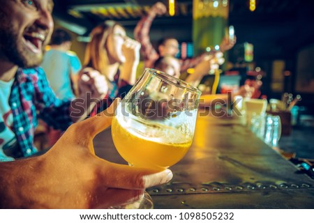 Sport, people, leisure, friendship, entertainment concept - happy male and female football fans or good yuong friends drinking beer, celebrating victory at bar or pub. Human positive emotions concept #1098505232