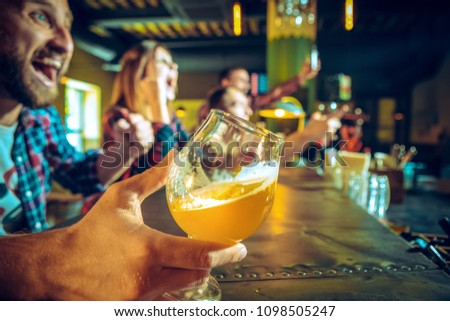Sport, people, leisure, friendship, entertainment concept - happy male and female football fans or good yuong friends drinking beer, celebrating victory at bar or pub. Human positive emotions concept #1098505247