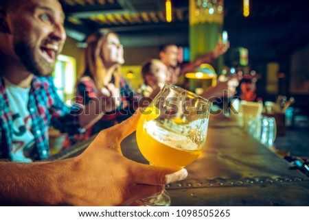 Sport, people, leisure, friendship, entertainment concept - happy male and female football fans or good yuong friends drinking beer, celebrating victory at bar or pub. Human positive emotions concept #1098505265