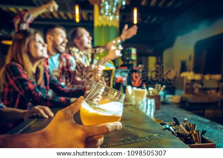 Sport, people, leisure, friendship, entertainment concept - happy male and female football fans or good yuong friends drinking beer, celebrating victory at bar or pub. Human positive emotions concept #1098505307