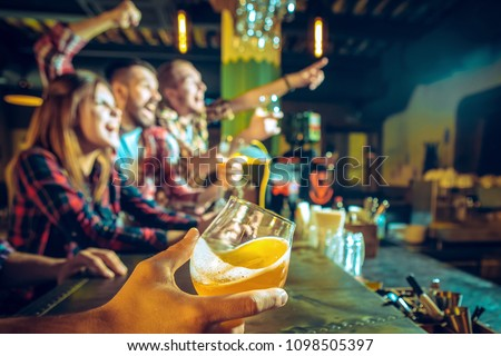 Sport, people, leisure, friendship, entertainment concept - happy male and female football fans or good yuong friends drinking beer, celebrating victory at bar or pub. Human positive emotions concept #1098505397