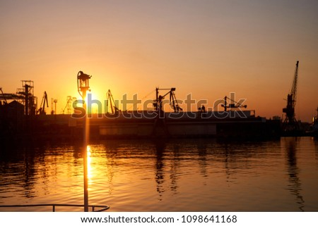 Magnificent sunset over the sea in port silhouettes of ships #1098641168