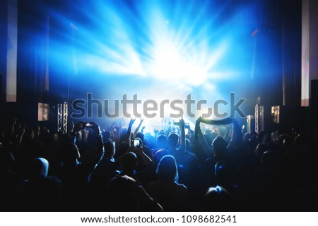 Silhouettes of people in a bright in the pop rock concert in front of the stage. Hands with gesture Horns. That rocks. Party in a club #1098682541