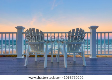 Empty Adirondack chair on a deck balcony overlooking the beach and the ocean at sunset Royalty-Free Stock Photo #1098730202