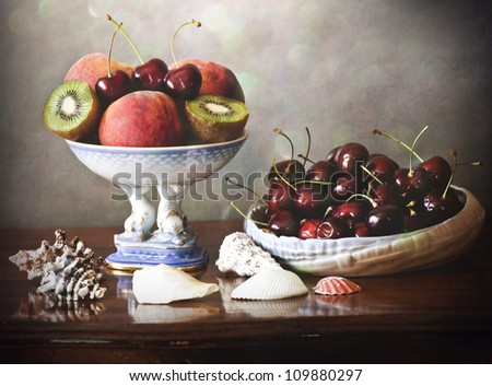 Still life with a porcelain tray full of peaches,kiwi,cherries, a porcelain basket with cherries on a wooden table decorated with shells #109880297