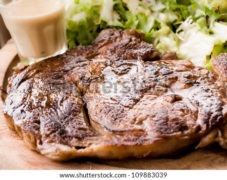 Grilled steak - Grilled meat ribs on the plate with hot sauce #109883039