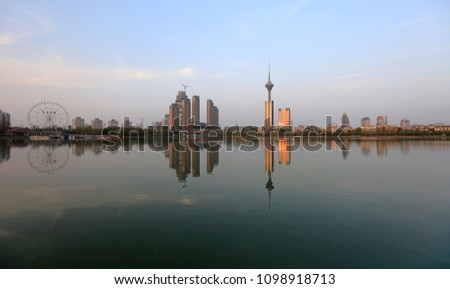 Beautiful view of the city of Tianjin with reflection in the water of the lake in the evening, China #1098918713