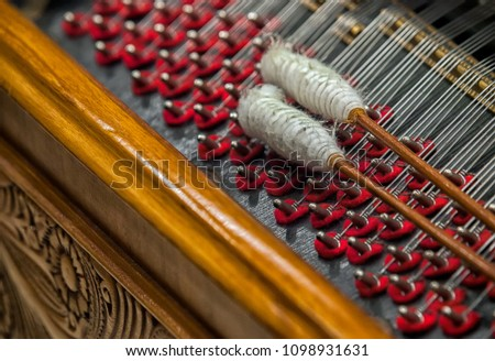 Cymbal,Cimbalom or Cembalon selective focus.Close up of  strings and wound beaters.The cimbalom is a concert hammered dulcimer,a type of chordophone. Cymbal is a very special string music instrument. #1098931631