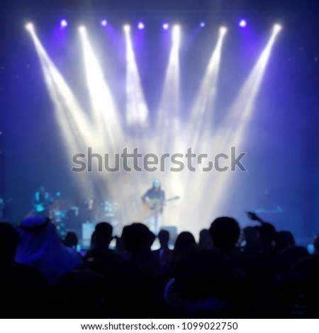 concert guitarlist in spotlight and crowd of people #1099022750
