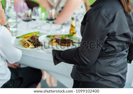 Waitress is carrying three plates with meat dish and vegetables #1099102400