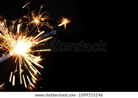Sparkler background / A sparkler is a type of hand-held firework that burns slowly while emitting colored flames, sparks, and other effects #1099155146