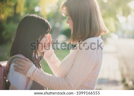 Asian mother saying goodbye to her daughter as she leave for School,back to school concept #1099166555