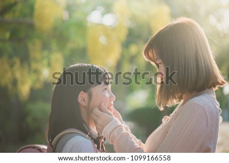 Asian mother saying goodbye to her daughter as she leave for School,back to school concept #1099166558