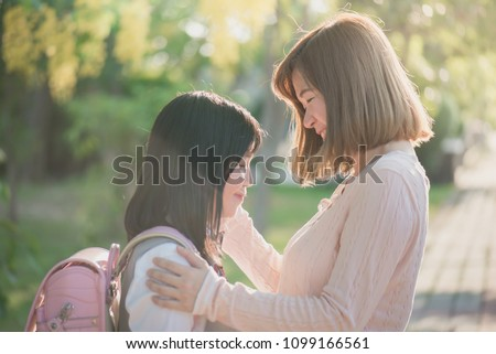 Asian mother saying goodbye to her daughter as she leave for School,back to school concept #1099166561