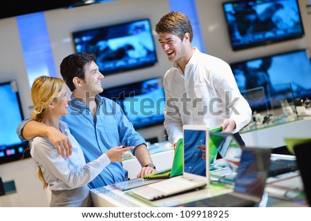 Young couple in consumer electronics store looking at latest laptop, television and photo camera Royalty-Free Stock Photo #109918925