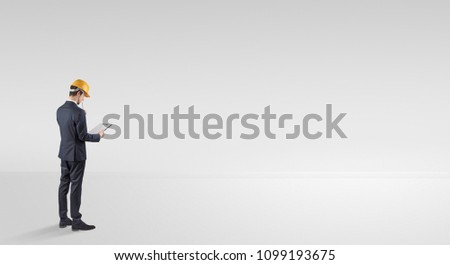 Young architect with construction helmet standing in an empty space and holding a plan #1099193675