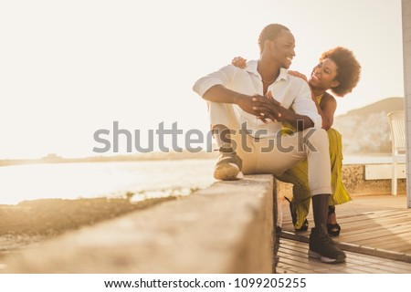 beautiful black race african couple in love and vacation sit down enjoying together with big smiles and laugh. casual clothes like fashion style with nice sunset backlight on the background. tenerife. #1099205255