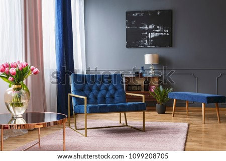 Real photo of a blue, wide chair standing on a rug in a spacious living room interior with grey walls and wooden floor next to a shelf and a table #1099208705