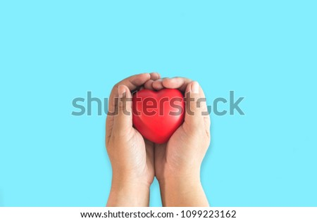 hand holding Red heart on blue background.top view health concept #1099223162