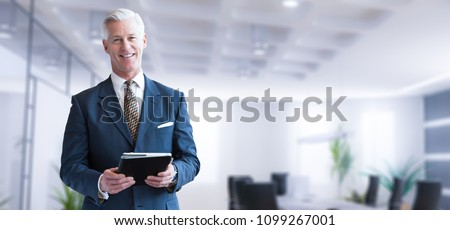Portrait of senior businessman using tablet in front of his modern office Royalty-Free Stock Photo #1099267001