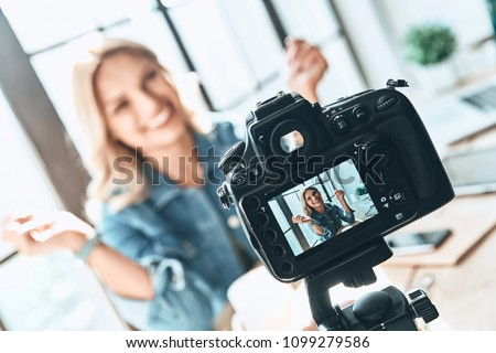 Filming. Beautiful young woman in casual wear smiling while recording video #1099279586