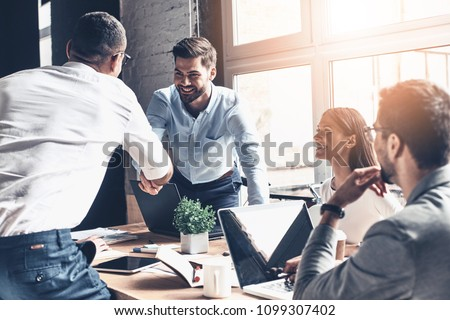 Glad to work with you! Young modern men in smart casual wear shaking hands and smiling while working in the creative office #1099307402