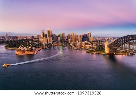 Pink colourful sunrise over Sydney city CBD landmarks on Sydney Harbour shores touched by steel arch of the Harbour bridge with passenger ferry on route to wharf. #1099319528