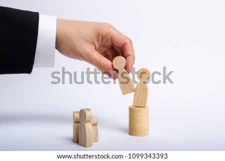 The man's hand of a businessman in a business suit holds a wooden figure of a man in his hand and moves another figure from his post. The concept of firing an employee, the replacement of staff #1099343393