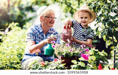 Gardening with kids. Grandmother and her grandchild enjoying in the garden with flowers. Hobbies and leisure, lifestyle, family life  #1099365908