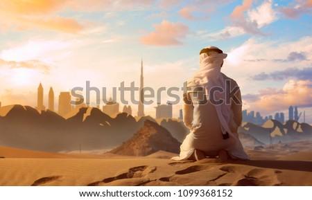 Arab Emirati man praying on top of a dune in UAE desert front Dubai skyline. Royalty-Free Stock Photo #1099368152