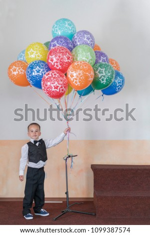 Boy 4 years holding colorful balloons. Happy boy on the stage holding balloons