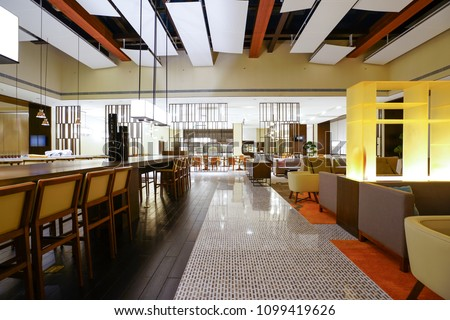 Hotel lobby interior with reception desk, marble floor and crystal lamp, sofas and long bar. #1099419626