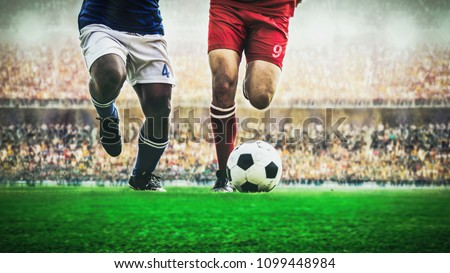 Two soccer football player dribbling a ball during match in the stadium Royalty-Free Stock Photo #1099448984