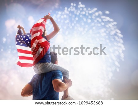 Patriotic holiday. Child sitting on shoulders of her father and  holding the Flag of the USA. America celebrate 4th of July. #1099453688