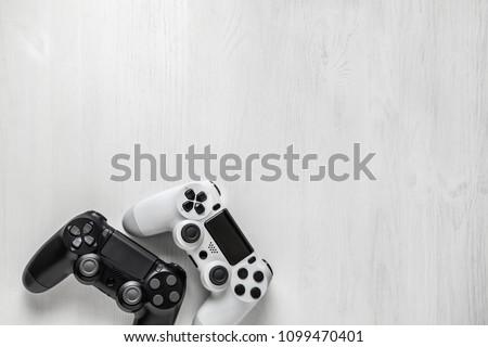 black and white modern gamepad on white wooden background