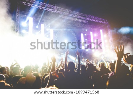 Young people dancing and having fun in summer festival party outdoor - Crowd with hands up celebrating fest concert event - Soft focus on left hand with yellow background flare #1099471568
