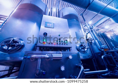 Modern interior of a brewery. Barrels and pipes. Factory interior. Industry background #1099475258