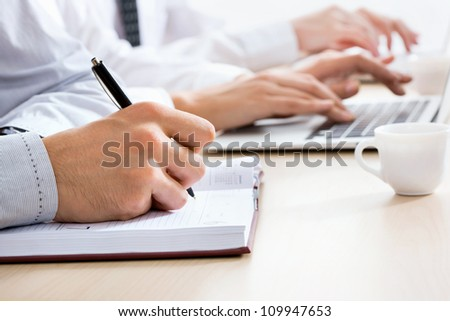 Businessman's hand writing in a notepad #109947653