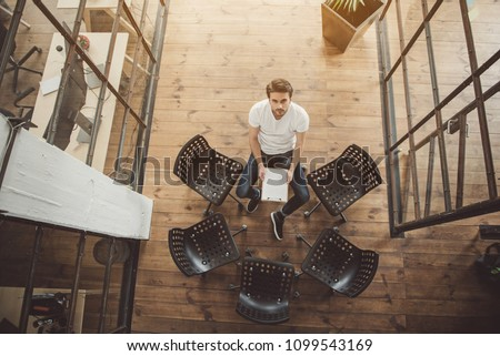 Top view full length portrait of serene male looking at camera while sitting near chairs and holding document in hands #1099543169