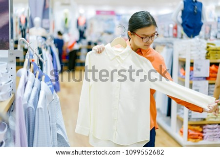 Asian attractive smart working women choosing shirt in sale discount season at shopping center. She try to put over it on her body for compare size. #1099552682