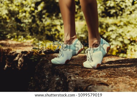 A young girl in sneakers jumps on rocks in a forest in summer  #1099579019